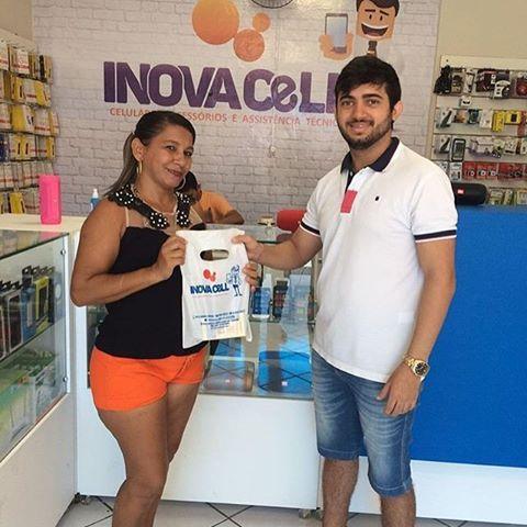 Neidinha recebendo das mãos de Thiago Luã o aparelho celular sorteado pela loja InovaCell.