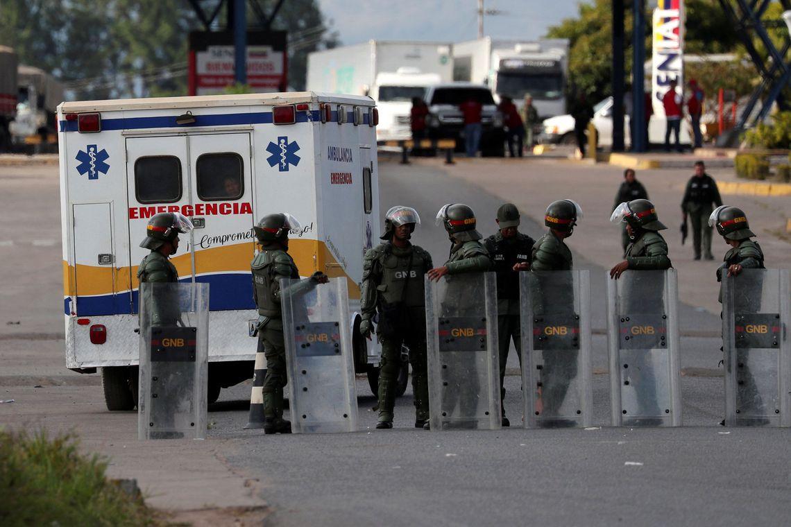 Uma ambulância transportando indígenas feridos passa ao lado de guardas nacionais venezuelanos no caminho de volta à Venezuela, na fronteira entre a Venezuela e o Brasil, em Pacaraima.