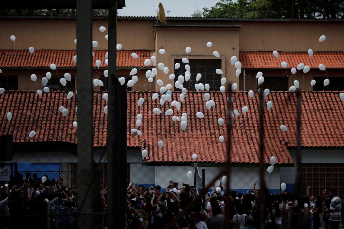 Alunos soltam balões durante homenagem às vítimas do tiroteio na escola Raul Brasil em Suzano, no dia da reabertura da escola.