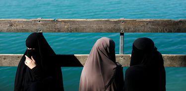 Alaa (L), 21, Amina (C), 24, e Nayab, 18, sentam-se em uma doca durante uma visita a Karlstrup Kalkgrav, um lago perto de Karlstrup localizado fora de Copenhague, Dinamarca, 19 de julho de 2018. REUTERS / Andrew Kelly
