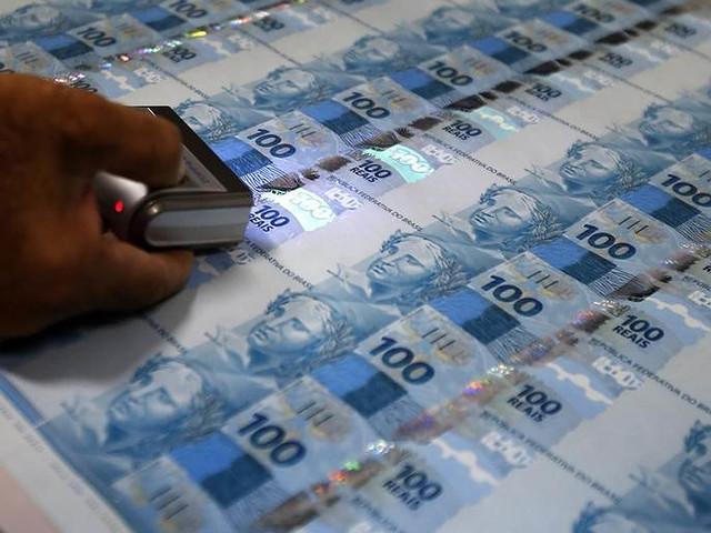 Funcionário inspeciona notas de 100 reais recém impressas na Casa da Moeda