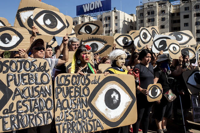 Demonstrators hold placards depicting eyes -in reference to police pellets reaching demonstrators' eyes- during a protest against Pinera's government in Santiago, on December 10, 2019. - Pinera promissed, during commemoration this Tuesday of the International Day of Human rights, support for victims of human rights violations by security forces during protests in Chile, and a firm commitment to achieve truth and justice. (Photo by Martin BERNETTI / AFP)