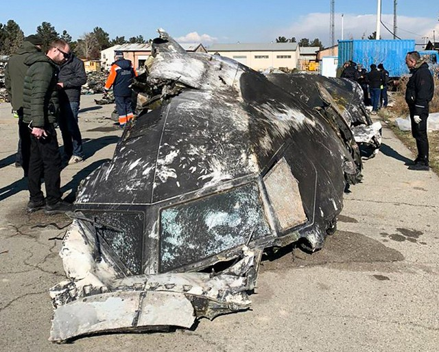 """This handout photograph taken and released on January 11, 2019, by The National Security and Defense Council of Ukraine, shows people standing and analysing the fragments and remains of the Ukraine International Airlines plane Boeing 737-800 that crashed outside the Iranian capital Tehran on January 8, 2020. - Iran said on January 11, 2020 it """"unintentionally"""" shot down a Ukrainian passenger jet, killing all 176 people aboard, in an abrupt about-turn after initially denying Western claims it was struck by a missile. Iranian president said a military probe into the tragedy had found """"missiles fired due to human error"""" brought down the Boeing 737, calling it an """"unforgivable mistake"""". (Photo by STR / National Security and Defense Council of Ukraine / AFP) / RESTRICTED TO EDITORIAL USE - MANDATORY CREDIT """"AFP PHOTO /  National Security and Defense Council of Ukraine"""" - NO MARKETING NO ADVERTISING CAMPAIGNS - DISTRIBUTED AS A SERVICE TO CLIENTS"""