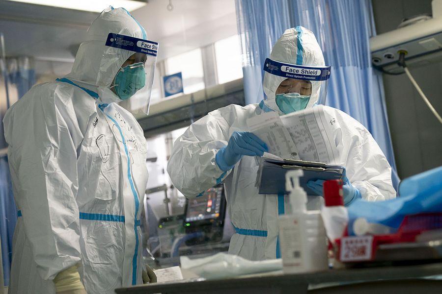Peng Zhiyong (D), chefe do departamento de medicina intensiva do Hospital Zhongnan, revisa registros diagnósticos de um paciente junto com seu colega na UTI do Hospital Zhongnan da Universidade de Wuhan, na Província de Hubei, centro da China, em 24 de janeiro de 2020. (Xinhua/Xiong Qi)